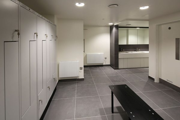 Changing area with a white bespoke locker system - Heathrow Approach
