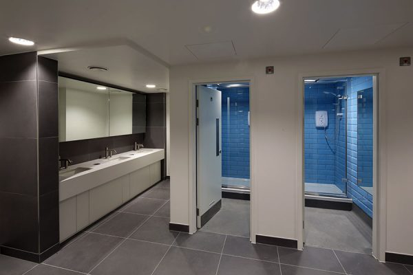 Staff shower and changing area features white Zodiac stone vanities - Heathrow Approach