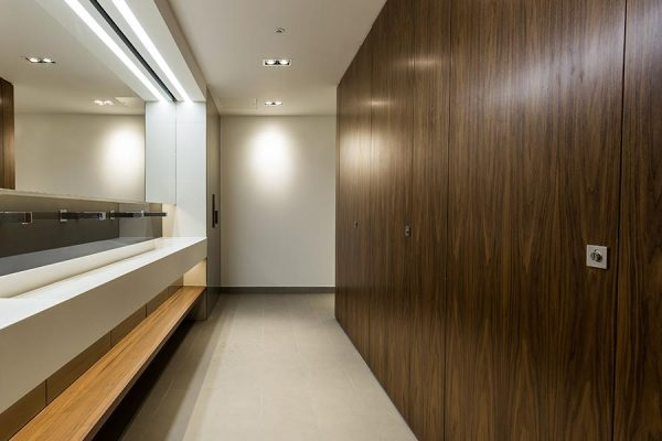 Real wood walnut veneer Alto toilet cubicles and White Corian trough-style vanity units - The Bower