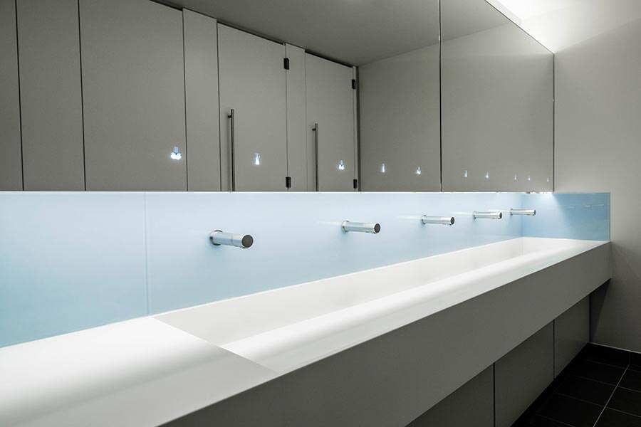 Corian trough-style vanity units and Tego hinged mirror system - Ziggy Stardust office project