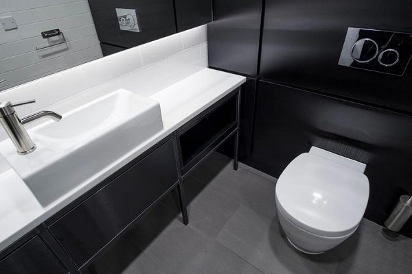 Unisex Superloo featuring black brushed metallic effect duct panels and Corian vanity units at 20-23 Mandela Street, London