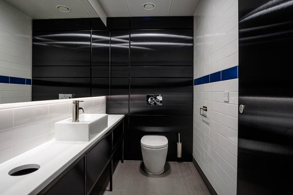 Unisex Superloo featuring black brushed metallic effect duct panels and Corian vanity units at 20-23 Mandela Street, London