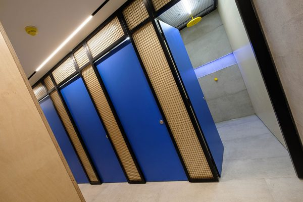 Vibrant blue Marcato shower cubicles in blue with pilaster in birch overlaid with black mesh at One Poultry, London