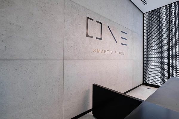 Concrete faced wall panelling with One Smart's Place logo in the reception area