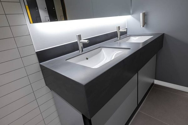 Arpeggio solid surfacing vanity units in light grey concrete-effect finish